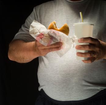 Man Eating Hamburger with Soda