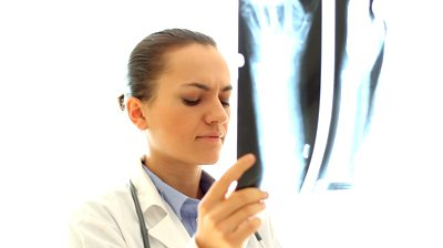 stock-footage-female-doctor-looking-at-xray-photo-isolated-on-white