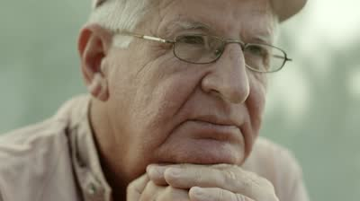 stock-footage-seniors-portrait-sad-elderly-man-with-white-hat-and-glasses-looking-at-camera